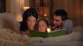Счастливая книга чтения семьи в кровати дома сток-видео