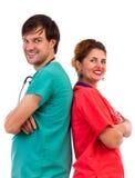 Счастливая команда 2 докторов стоя назад к задней части при сложенные рукоятки Стоковая Фотография