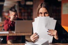 Счастливая коммерсантка пряча за документами в кафе Стоковая Фотография