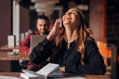 Счастливая коммерсантка сидя на таблице и говоря на телефоне в кафе бородатый фрилансер на заднем плане Стоковое Фото