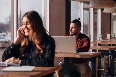 Счастливая коммерсантка сидя на таблице и говоря на телефоне в кафе бородатый фрилансер на заднем плане Стоковое фото RF