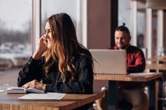 Счастливая коммерсантка сидя на таблице и говоря на телефоне в кафе бородатый фрилансер на заднем плане Стоковые Фотографии RF