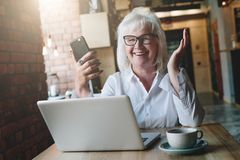 Счастливая коммерсантка сидя на таблице перед компьтер-книжкой, держа Стоковые Фотографии RF