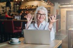 Счастливая коммерсантка сидя на таблице перед компьтер-книжкой, держа руки поднимающий вверх и усмехаясь, работа, уча Стоковые Изображения RF