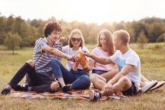 Счастливая компания друзей clink бутылки с холодным сидром или пиво, сидит близко к одину другого, празднует успешно сданные экза стоковые изображения rf
