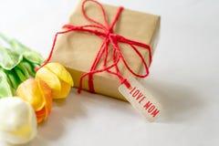 Счастливая концепция дня ` s матери Подарочная коробка и цветок, бумажная бирка с текстом МАМЫ ВЛЮБЛЕННОСТИ Стоковое Изображение RF