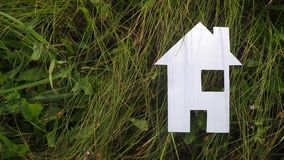 Счастливая концепция дома конструкции семьи бумажный дом стоит в зеленой траве в природе видео экологичности символа жизни сток-видео