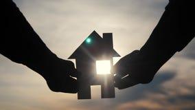 Счастливая концепция дома конструкции семьи человек держа домой бумажный дом в его образе жизни рук на силуэте захода солнца видеоматериал