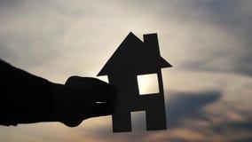 Счастливая концепция дома конструкции семьи человек держа домой бумажный образ жизни дома в его руках на силуэте захода солнца видеоматериал