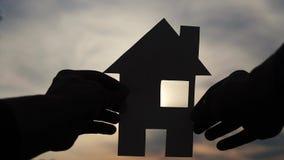 Счастливая концепция конструкции дома семьи человек держа домашний образ жизни бумажный дом в его руках на силуэте захода солнца акции видеоматериалы