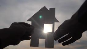 Счастливая концепция конструкции дома семьи человек держа домой бумажный дом в его руках на силуэте образа жизни захода солнца видеоматериал