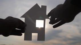 Счастливая концепция конструкции дома семьи человек держа домой бумажный дом в его руках на солнечном свете силуэта захода солнца сток-видео