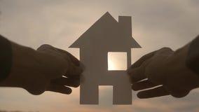 Счастливая концепция конструкции дома семьи человек держа домой бумажный дом в его руках на солнечном свете силуэта захода солнца видеоматериал