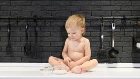 Счастливая концепция chilhood Милый мальчик сидя на таблице пробуя сахар и помадки с его пальцем 4K видеоматериал