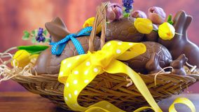 Счастливая корзина пасхи яичек шоколада и кроликов зайчика в большой корзине Стоковые Изображения RF