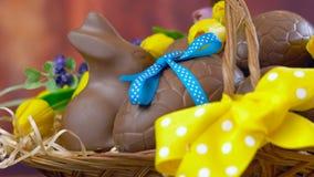 Счастливая корзина пасхи яя шоколада и кроликов зайчика в большой корзине, тележке акции видеоматериалы
