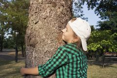 Счастливая красивая девушка обнимая большое дерево в парке любящая природа стоковое фото