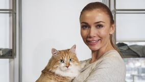 Счастливая красивая женщина прижимаясь с ее шикарным котом имбиря стоковые изображения rf