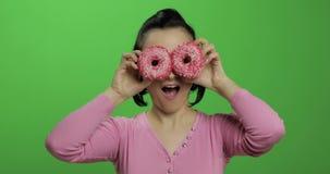 Счастливая красивая маленькая девочка представляя и имея потеху с donuts o акции видеоматериалы
