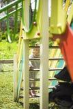 Счастливая красивая маленькая девушка redhead взбирается скольжение на спортивной площадке стоковое фото rf