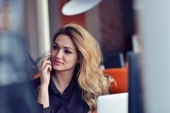 Счастливая красивая молодая бизнес-леди сидя и говоря на сотовом телефоне в офисе стоковое фото rf