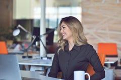 Счастливая красивая молодая бизнес-леди сидя и говоря на сотовом телефоне в офисе стоковое изображение
