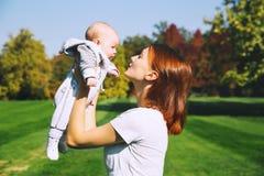 Счастливая красивая молодая мать с ее ребенком младенца на природе Стоковая Фотография