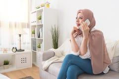 Счастливая красивая мусульманская женщина разговаривая с другом стоковые фотографии rf