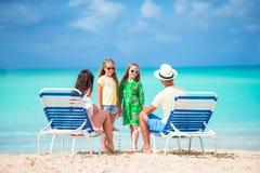 Счастливая красивая семья из четырех человек на пляже Родители ослабляя на sunbed и дети имея потеху на побережье Стоковые Фотографии RF