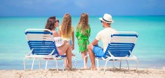 Счастливая красивая семья из четырех человек на пляже Родители ослабляя на sunbed и дети имея потеху на побережье Стоковое Фото