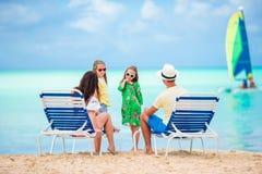 Счастливая красивая семья из четырех человек на пляже Родители ослабляя на sunbed и дети имея потеху на побережье Стоковое Изображение