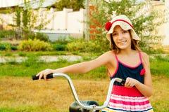 Счастливая красивейшая девушка с велосипедом на заходе солнца Стоковое Изображение RF