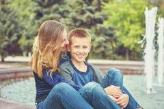 Счастливая красивые мать и сын наслаждаясь около фонтана стоковая фотография
