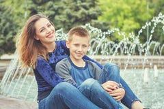 Счастливая красивые мать и сын наслаждаясь около фонтана стоковые фотографии rf