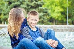 Счастливая красивые мать и сын наслаждаясь около фонтана стоковое фото rf