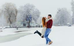 Счастливая любящая пара имеет потеху в лесе зимы человек закручивает вокруг его красивой красной головной женщины во время Стоковая Фотография RF