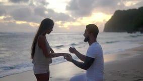 Счастливая любящая пара на пляже песка океана, парне получает на колене и делает предложение акции видеоматериалы