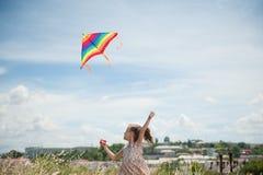 Счастливая малая девушка при длинные волосы держа змея летания в поле на день лета солнечный Стоковая Фотография RF