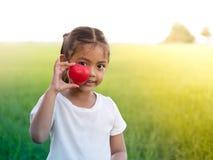 Счастливая маленькая азиатская девушка держа красные сердце и усмехаться Стоковые Изображения