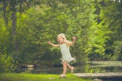 Счастливая маленькая девочка бежать в лесе в лете Стоковые Изображения RF