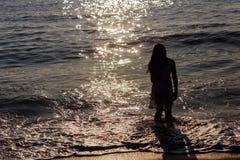 счастливая маленькая девочка бежит вдоль морского побережья восхода солнца позади Стоковая Фотография RF