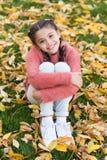 Счастливая маленькая девочка в листьях и природе осени леса осени Малый ребенок с листьями осени детство счастливое школа стоковое фото