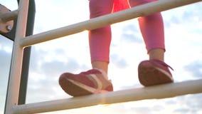 Счастливая маленькая девочка в стильной бейсбольной кепке взбирается вверх лестницы на заходе солнца сток-видео