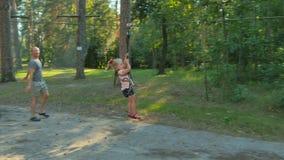 Счастливая маленькая девочка едет на ropeway в парке веревочки видеоматериал