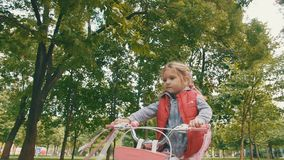 Счастливая маленькая девочка ехать велосипед в внешнем сток-видео