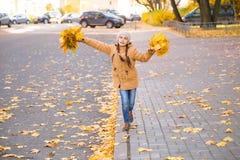 Счастливая маленькая девочка идя на обочину через упаденные листья на тротуаре в городе осени стоковые фотографии rf