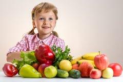 Счастливая маленькая девочка и много фрукт и овощ Стоковые Фото