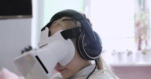 Счастливая маленькая девочка наблюдает шарж в наушниках и стеклах виртуальной реальности видеоматериал