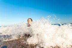 Счастливая маленькая девочка наслаждаясь в море брызгая волны среднеземноморск Стоковое фото RF