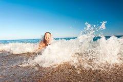 Счастливая маленькая девочка наслаждаясь в море брызгая волны среднеземноморск Стоковое Изображение